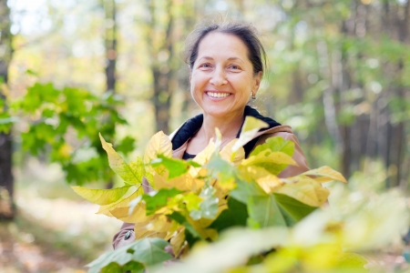 seasonable: Portrait of  laughing mature woman  in autumn park