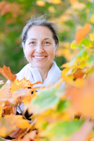 Portrait of happy mature woman  in autumn park Stock Photo - 20279640