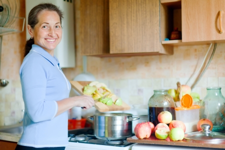 pots and pans: Mature woman cooks applesauce jam in kitchen