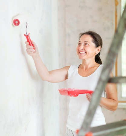 Happy mature woman makes repairs at home Stock Photo - 20279544