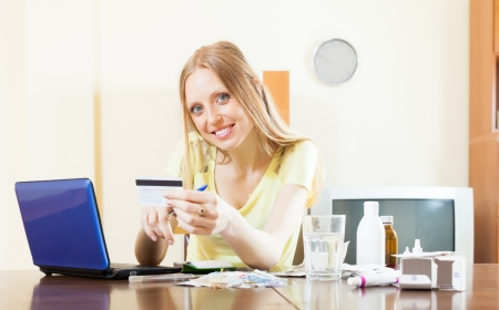 troche: happy woman shopping medications on internet from home, using laptop and paying with  card