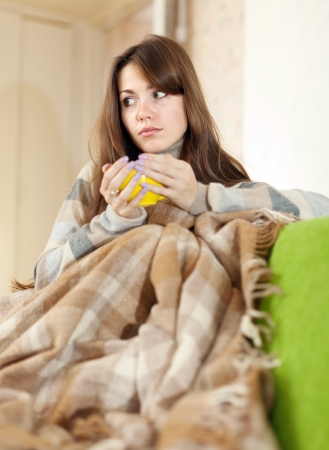 casualy: Relaxed woman sitting  on sofa in livingroom enjoying drinking coffee  Stock Photo