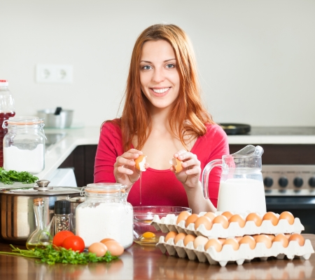 Smiling housewife in red making eggs  in domestic kitchen photo