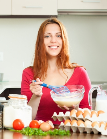 Smiling housewife in red making eggs  in domestic kitchen Stock Photo - 20311972