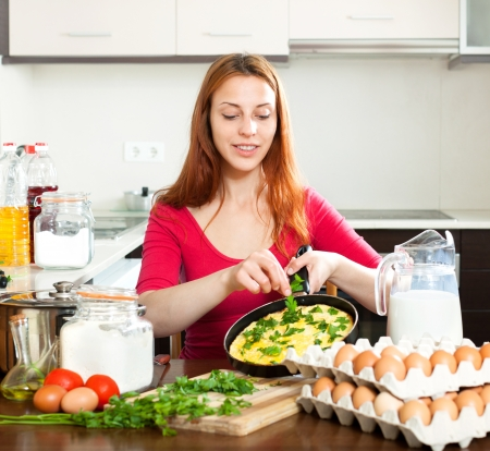 Smiling woman in red with scrambled eggs in pan at  kitchen Stock Photo - 20311971