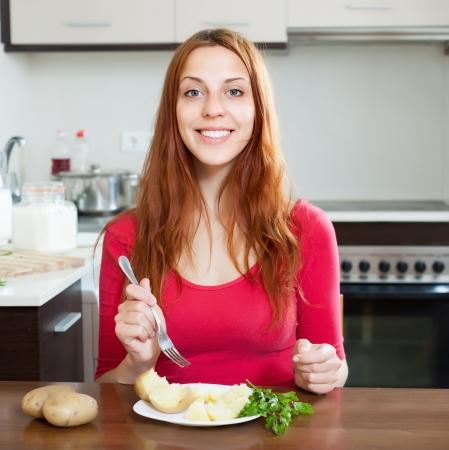Happy  woman eating jacket potatoes at home inter Stock Photo - 20311956
