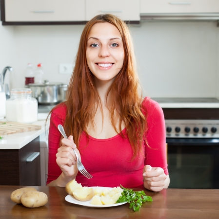 Happy  woman eating jacket potatoes at home interior Stock Photo - 20311956