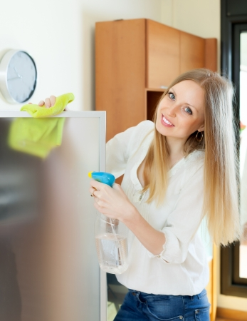 Positive blonde housewife cleaning  glass Stock Photo - 20312090
