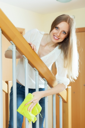 Pretty long-haired housewife cleaning stair railings with rag at home  Stock Photo - 20311991