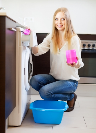 woman doing laundry with detergent at home