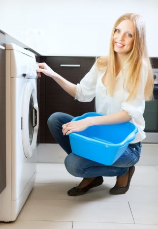 Long-haired woman using washing machine at home Stock Photo - 20311958