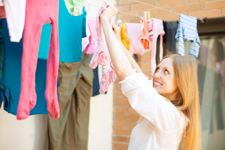 Positive long-haired girl drying clothes on clothesline  Imagens