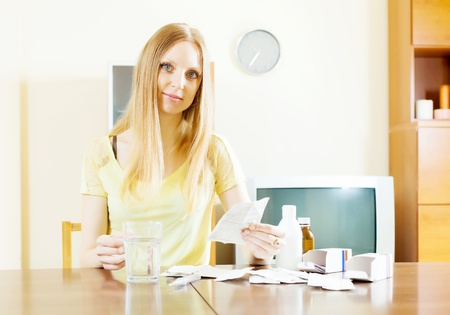troche: serious young woman with medications at home Stock Photo