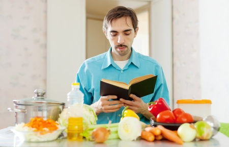 man reading cookbook for recipe in domestic kitchen at home photo