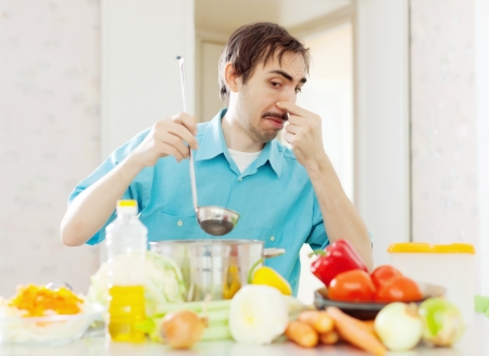 frowy: Man with foul food at kitchen Stock Photo
