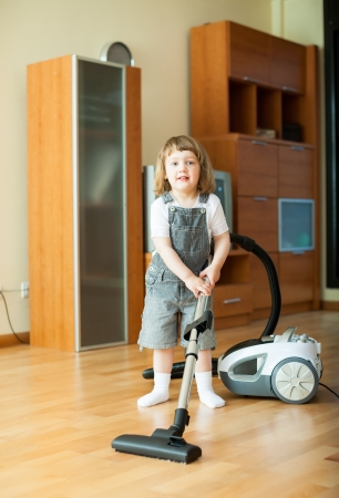 girl with vacuum cleaner on parquet floor in  room photo