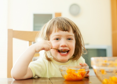 carroty:  2 years  child eats carrot salad with spoon in home Stock Photo