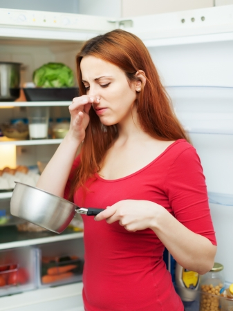 frowy:  woman in red with foul food near   refrigerator Stock Photo