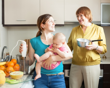 Happy women with child together cooking fruit puree  in kitchen at home Stock Photo - 20433453