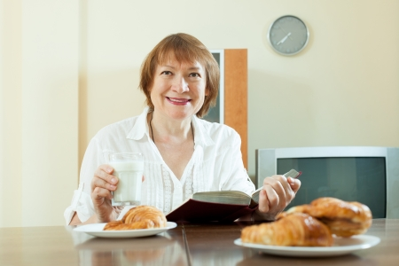 Happy mature woman reading book during breakfast with croissants in morning at home  photo