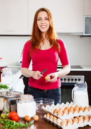 Woman cracking eggs into bowl in kitchen photo
