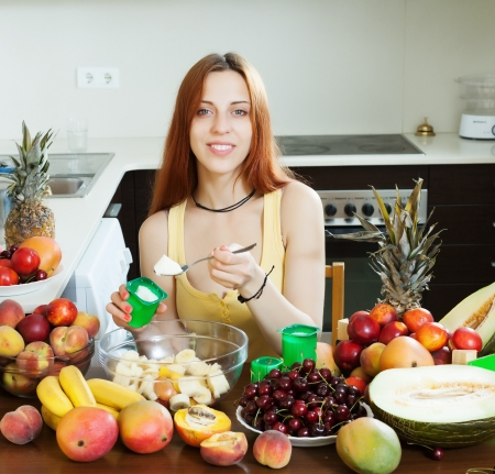 woman cooking fruit salad with yoghurt in home kitchen  photo