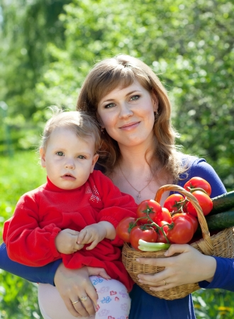 Happy woman and child with  harvested vegetables in garden Stock Photo - 20480003