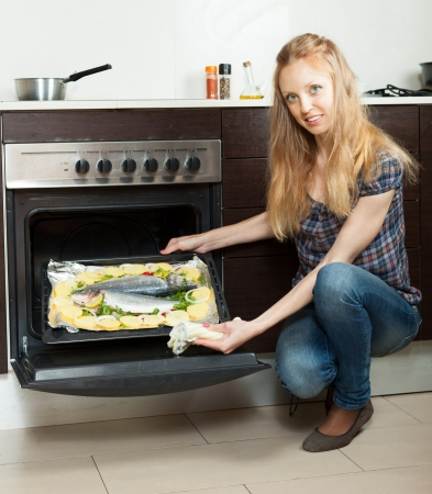 Long-haired housewife cooking fish and potatoes on sheet pan in oven at  kitchen  photo