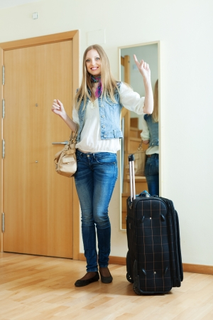 positive girl with luggage near door in home photo