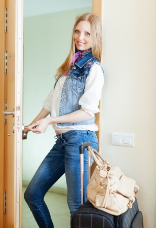 Blonde positive woman   loocking door and leaving her home photo