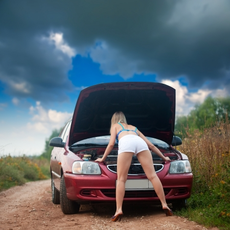 Sexy girl looking under the car hood  outdoor  photo