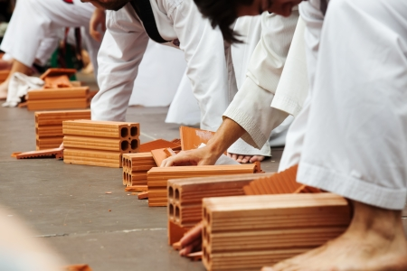 Few karate students show their skills by breaking bricks photo