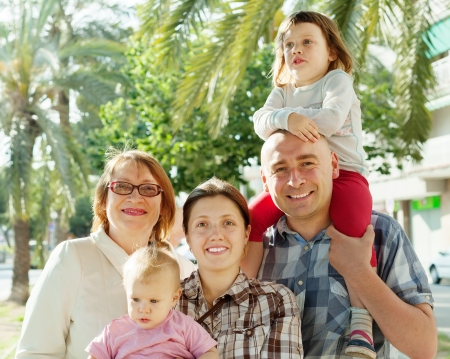 joyful parents with two children and grandmother at  street in summer Stock Photo - 20544814