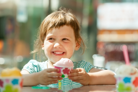 eating in: Happy 3 years girl eating ice cream at outdoor cafe in summer Stock Photo