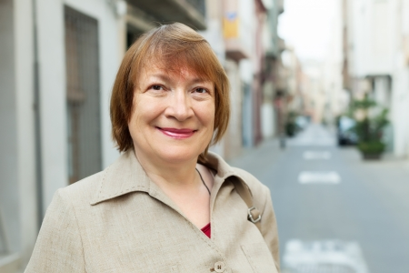 Outdoor portrait of european mature woman in old city street photo