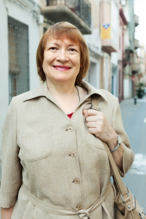 Outdoor portrait of positive senior woman at european city street photo