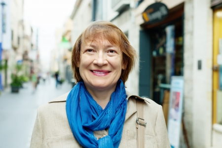 smiling mature woman wearing scarf in city street photo