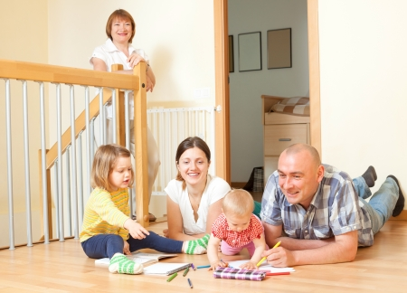 Portrait of  smiling happy three generations family sits on parquet floor in livingroom at home photo