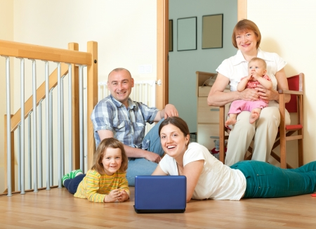 Portrait of smiling happy three generations family with two children and lap top on the floor photo
