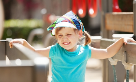 adroitness:  laughing three-year girl at playground area in sunny  day