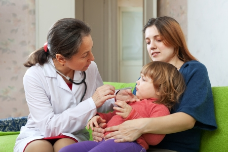 children's doctor: friendly mature childrens doctor examining 2 years child at home