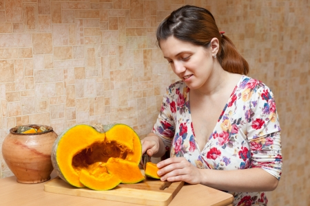 woman  cuts pumpkin in her kitchen  photo