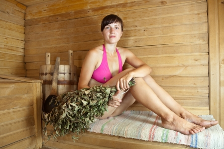 swelter: young brunette woman sitting in sauna