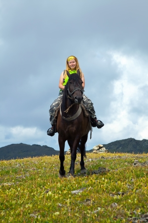 Femminile rider a cavallo alle montagne photo