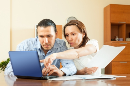 wistful: wistful couple calculating budget at home interior