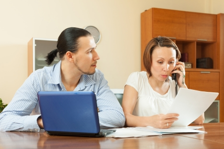 serious middle-aged Man and woman looking financial document at home photo