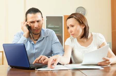 Adult couple calling by mobile about  documents at home interior photo