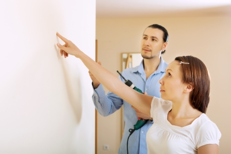 modifying: Middle-aged couple choosing point for hole in the wall at home Stock Photo