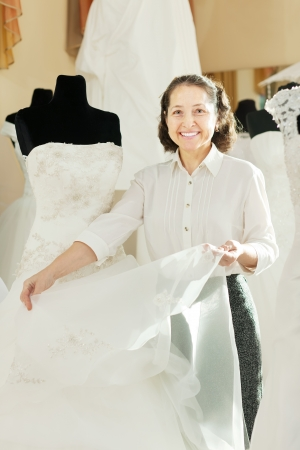Shop consultant shows bridal dress at wedding store photo