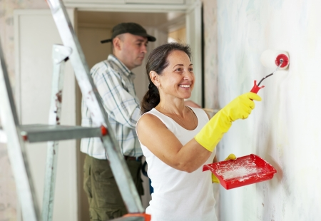 Smiling woman and man makes repairs in home interior together photo